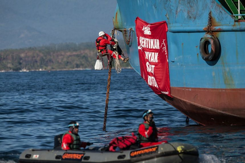 """Greenpeace activists climbing aboard a tanker to hang a banner reading """"Stop Dirty Palm Oil"""" in Indonesian at the Wilmar International refinery in Bitung, North Sulawesi, in September 2018."""