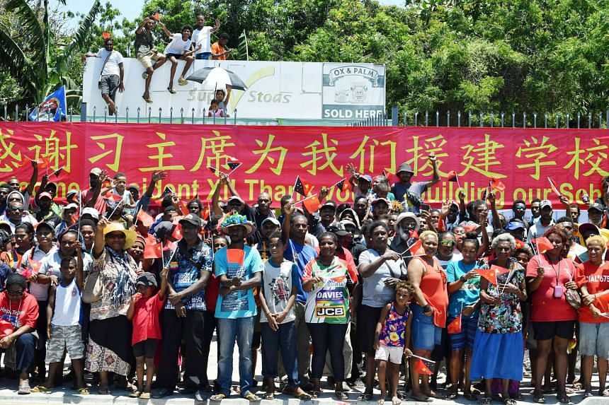 Above: Villagers in traditional costume going through security screening at an event attended by China's President Xi Jinping in Port Moresby yesterday. Right: Papuans waiting to welcome President Xi, who is the first Chinese leader to make a state v