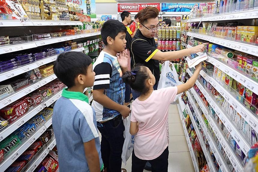Cheers area manager Ricky Tan, 34, helping beneficiaries of the fund shop at a Cheers convenience store. Each child was given $20 to buy whatever he or she wanted.