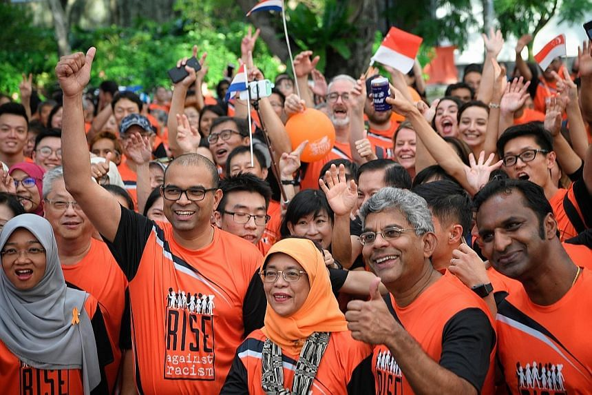 Close to 3,000 people showed up in support of the Rise Against Racism campaign yesterday at the Orange Ribbon Walk. They walked 3.8km around the Marina Bay area, accompanied by President Halimah Yacob (front, centre), who flagged off the walk at Espl