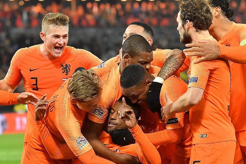 Netherlands midfielder Georginio Wijnaldum (kneeling) being congratulated by his teammates after opening the scoring against France just before half-time on Friday.