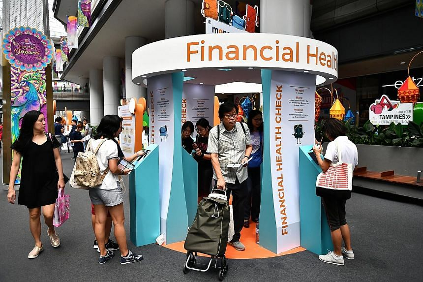 Visitors at the MoneySense roadshow at Our Tampines Hub yesterday. The new initiatives announced at the roadshow are part of government efforts to boost financial literacy among Singaporeans. Government agencies will also enhance their services to he