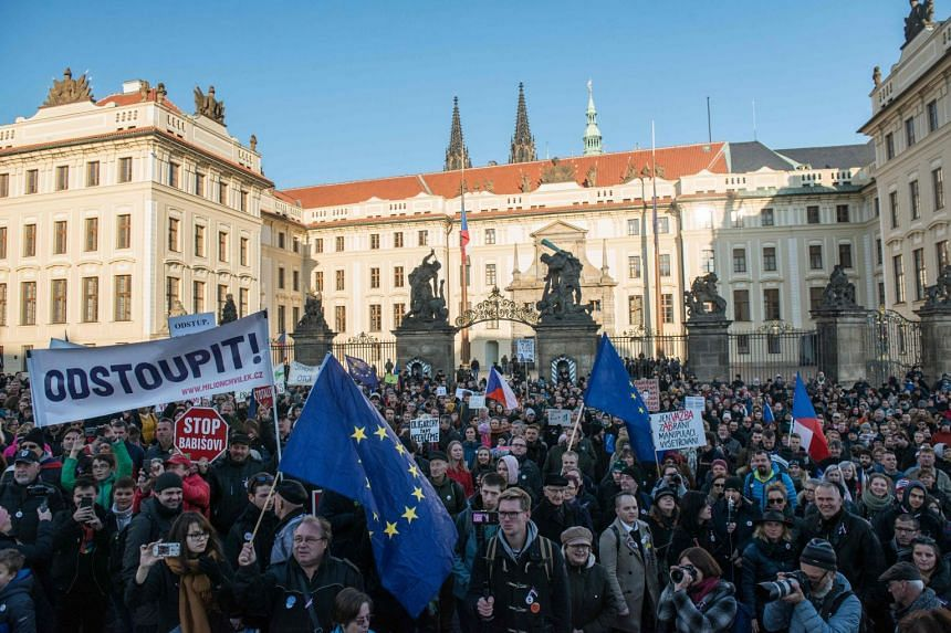 Demonstrators hold placards calling for the resignation of Czech Prime Minister Andrej Babis.