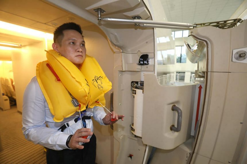 Civil Aviation Authority of Singapore staff demonstrates the correct use of a life vest in case of an emergency on the aircraft on Nov 9, 2018.