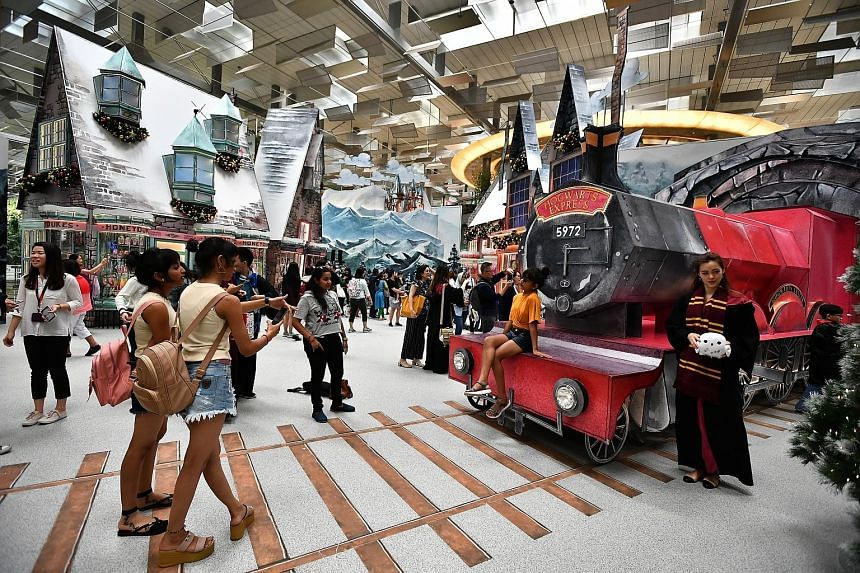 """Visitors soaking in the atmosphere at Hogsmeade Village, which has been recreated at Changi Airport's Terminal 3 Departure Hall. """"A Wizarding World Holiday at Changi"""" was launched last Friday, and features four life-size set-ups, inspired by prominen"""
