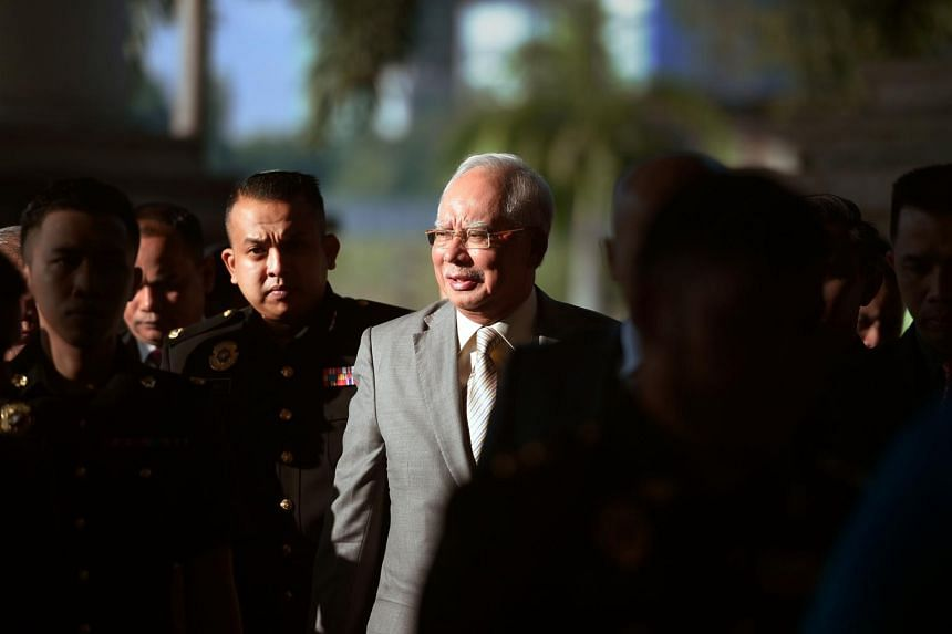 File photo of former Malaysian prime minister Najib Razak being escorted by police to the courthouse in Kuala Lumpur, on Oct 25, 2018.