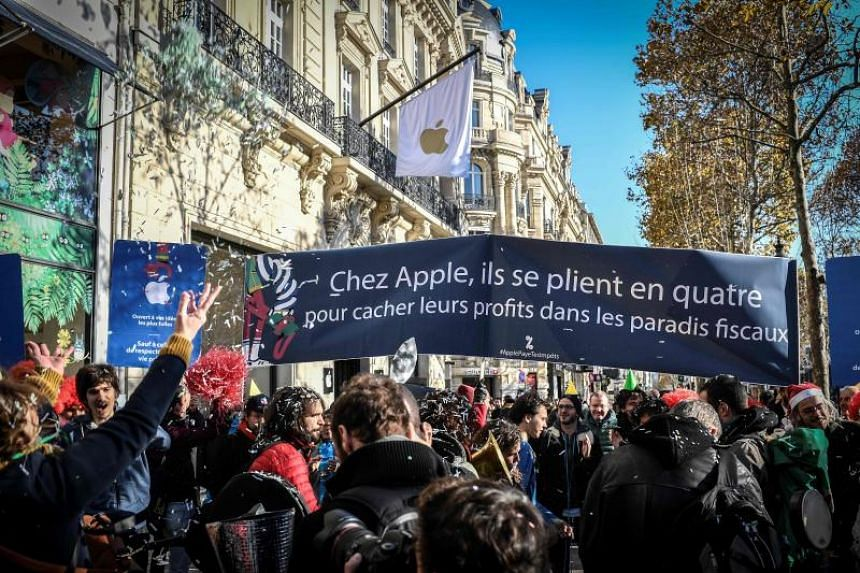 Activists from the Association for the Taxation of Financial Transactions and Citizen's Action (Attac) demonstrate during the opening of a new Apple store on the Champs Elysees boulevard in Paris to denounce tax avoidance on Nov 18, 2018.