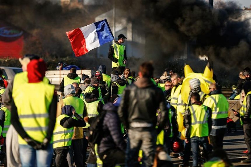 """People block Caen's circular road on Nov 18, 2018 in Caen, Normandy, on a second day of action, a day after a nationwide popular initiated day of protest called """"yellow vest""""  movement to protest against high fuel prices."""