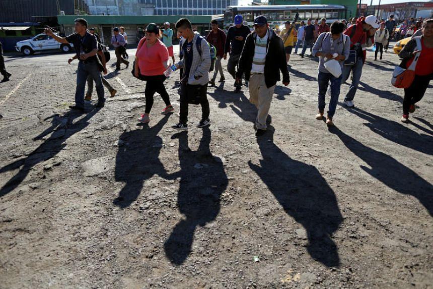 People in a caravan of migrants departing from El Salvador en route to the United States arrive at a bus terminal, in San Salvador, El Salvador, on Nov 18, 2018.