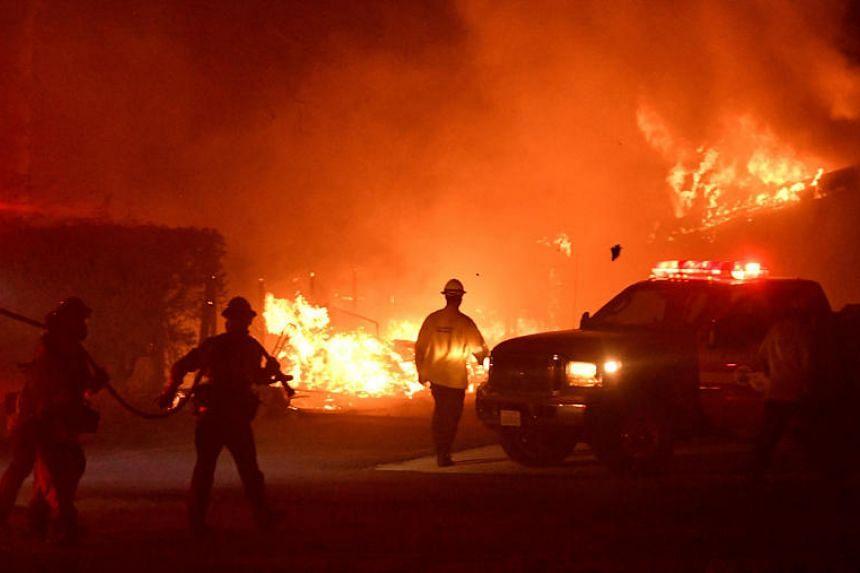 Firefighters work to put out the flames during the Woolsey Fire in Malibu, California, on Nov 9, 2018. Ms Deseriee Edman's family home in Malibu burned to the ground during the Woolsey Fire, a day after she survived a mass shooting.