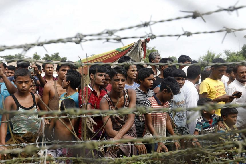 """Rohingya refugees gathering near a fence at the """"no man's land"""" zone at the Bangladesh-Myanmar border in Maungdaw district, Rakhine, on Aug 24, 2018"""