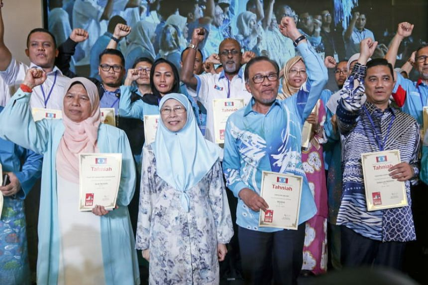 Outgoing People's Justice Party president and Malaysia's Deputy Prime Minister Wan Azizah Wan Ismail with her husband and the party's new president Anwar Ibrahim at the party's 13th National Congress in Shah Alam on Nov 18, 2018.