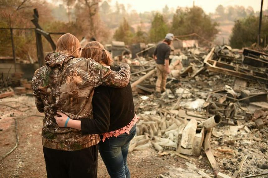 Kimberly Spainhower (left) hugs her daughter Chloe, while her husband Ryan Spainhower searches through the ashes of their burned home in Paradise, California on Nov 18, 2018.