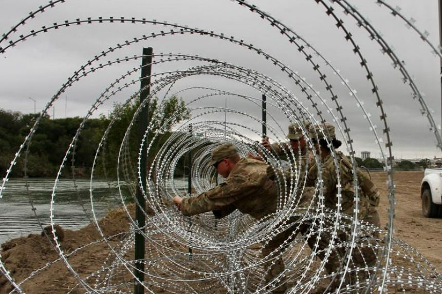 Soldiers installing barbed wire fences on the banks of the Rio Grande in Laredo, Texas, on Nov 18, 2018.