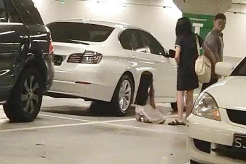 In the clip, the girl, who looks to be of primary school age, is seen kneeling next to a white car at the Ikea Tampines carpark.