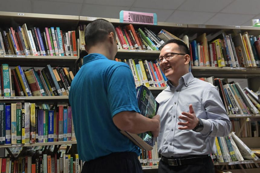 Mr Wong Yew Fei, a lecturer from Ngee Ann Polytechnic, speaks with an inmate at the Prison School on Nov 19, 2018.