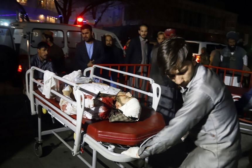 Afghan health workers transport an injured person outside a hospital for treatment after the attack.