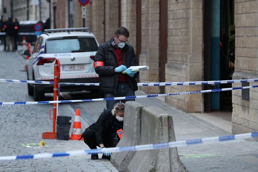 Police investigators work outside the police headquarters after a policeman was stabbed in Brussels.