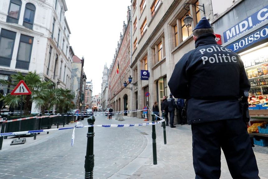 Police keep watch outside the police headquarters after a policeman was stabbed in Brussels.