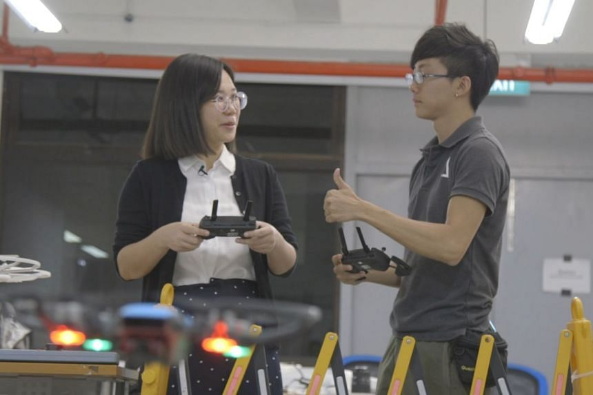 Host Toh Yan Wei (left) flies a drone indoors, under the supervision of full-time drone pilot Wei Ming Xian.