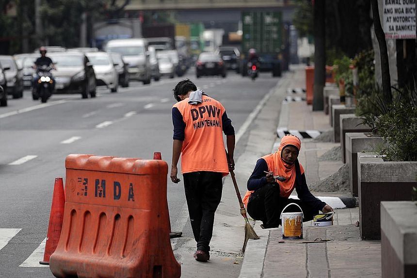 Workers yesterday painting a pavement in preparation for the state visit of Chinese President Xi Jinping. Philippine and Chinese officials are working to close at least two infrastructure deals during Mr Xi's visit.