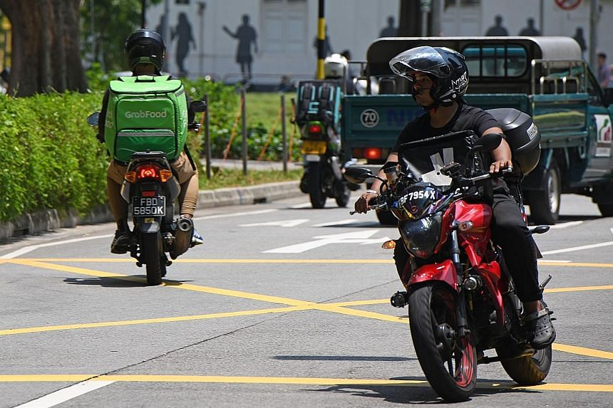 A GrabFood delivery rider (at left) in Singapore. According to the report from Google and Temasek, Singapore has the second-largest market in the region for ride-hailing services by value. This is partly due to higher fares for online transport rides