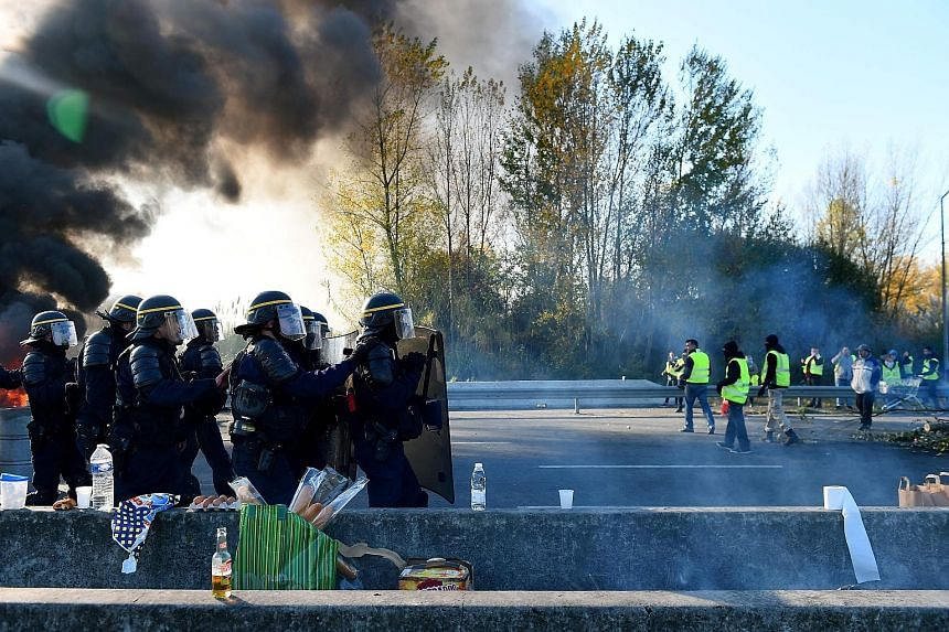 Riot police facing off against protesters opposing rising fuel prices in Bordeaux yesterday. Demonstrators blocked access to fuel depots and stopped traffic on major roads in France, after the government refused to back down on fuel tax hikes despite