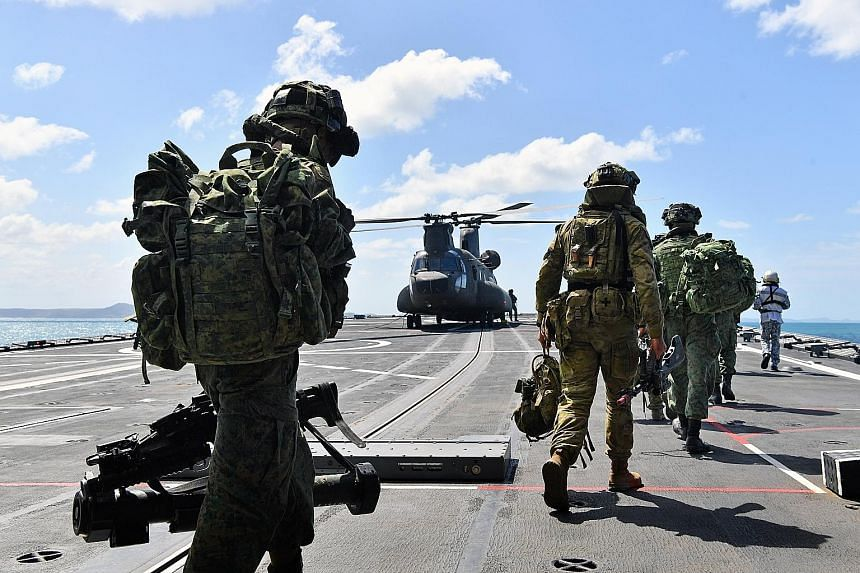 Troops from Singapore and Australia preparing to board a Chinook helicopter on the RSS Resolution as part of Exercise Trident in Australia earlier this month. In Parliament yesterday, Defence Minister Ng Eng Hen said the army is reviewing the experie