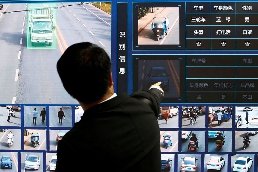 A man points at a screen showing a traffic surveillance software at the Security China 2018 exhibition on public safety and security in Beijing, on Oct 24, 2018.