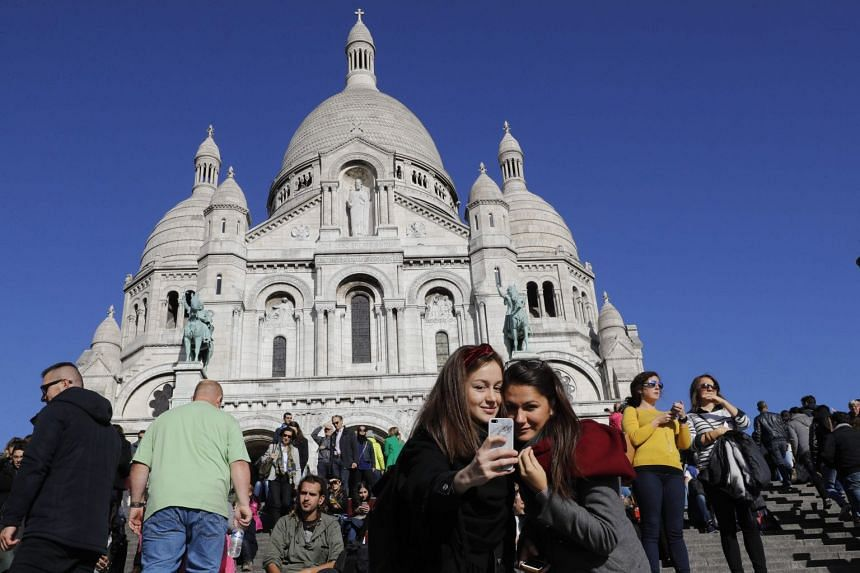 Tourists taking a selfie in front of the Sacre Coeur Basilica in the Montmartre district of Paris.