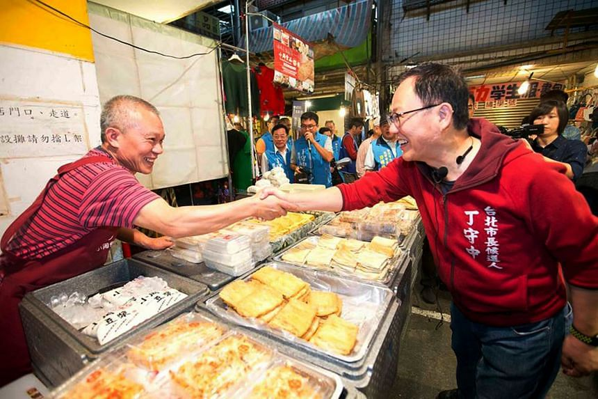 TAIPEI: Kuomintang's Taipei mayoral candidate Ting Shou-chung shaking hands with a vendor at a market in Taipei. He is in a neck-and-neck race with the incumbent Ko.