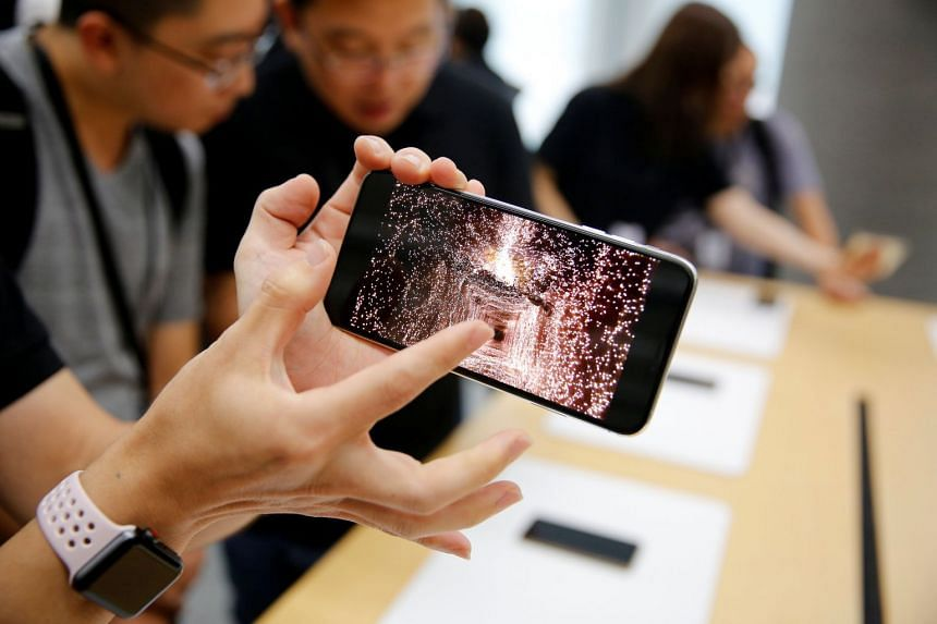 People handle the Apple iPhone XS and iPhone XS Max during a media tour at an Apple office in Shanghai, China.