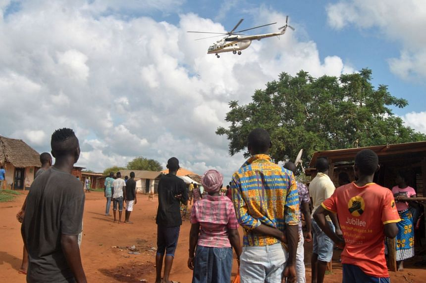 Residents look at a police helicopter patrolling near the house in which the Italian volunteer lived before she was seized.