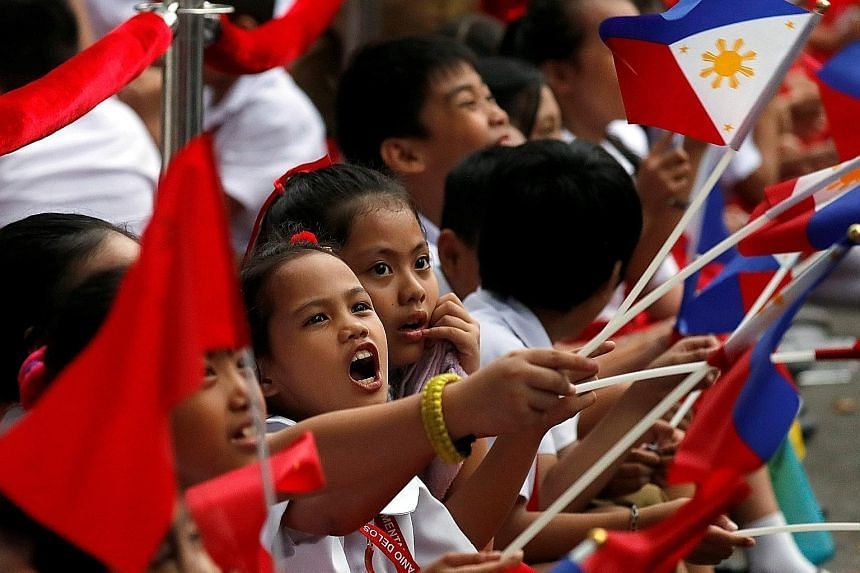 Schoolchildren waving the Philippine and Chinese national flags as they waited for the convoy of visiting Chinese President Xi Jinping near the Malacanang Presidential Palace in Manila yesterday. A Filipino protester making his views felt during a pr