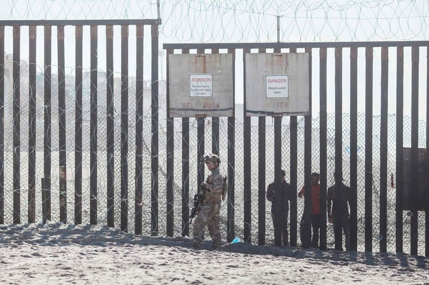 A member of the US military stands in front of the border fence that divides the US and Mexico at Friendship Park in San Diego, California.