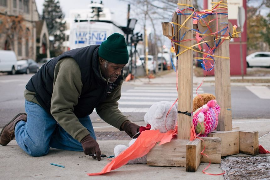 Ziff Sistrunk sets up crosses memorializing Dr Tamara O'Neal and pharmacy resident Dayna Less outside Mercy Hospital.