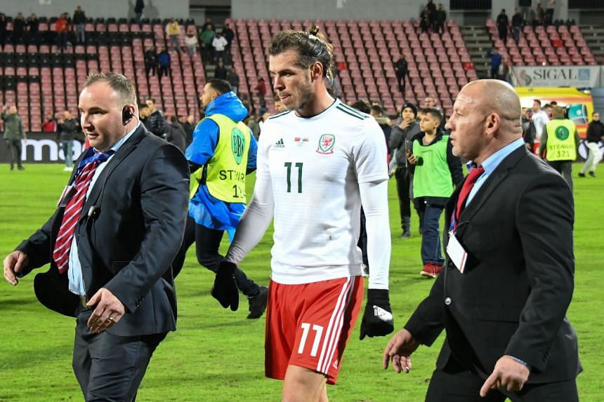 Wales' Gareth Bale (centre) is escorted by bodyguards as children try to take photos of him after the match.