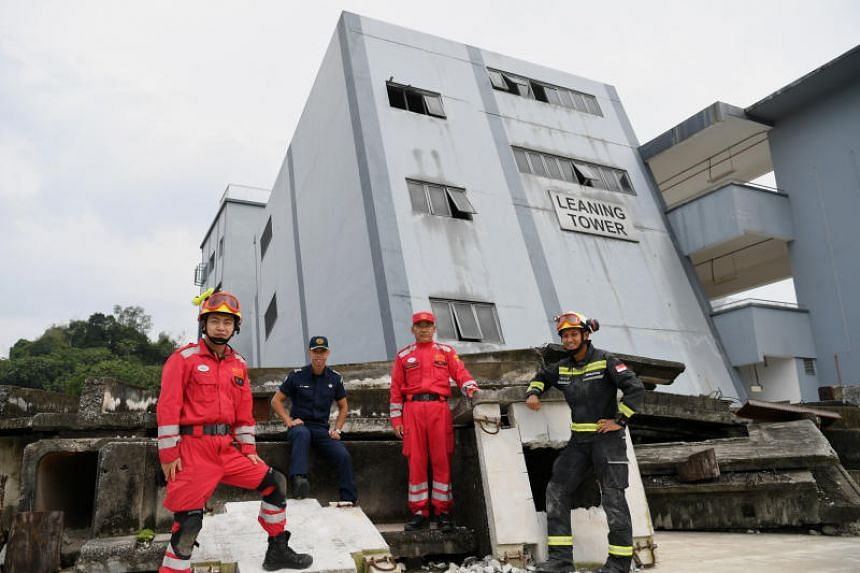 (From left) China International Search and Rescue (CISAR) Team member Zhang Yu, SCDF Lieutenant-Colonel Chew Keng Tok, CISAR leader Zhuang Qian Jiang, and SCDF Second Warrant Officer Mohammed Fayrus Abdul Rasit at the Home Team Tactical Centre, on No