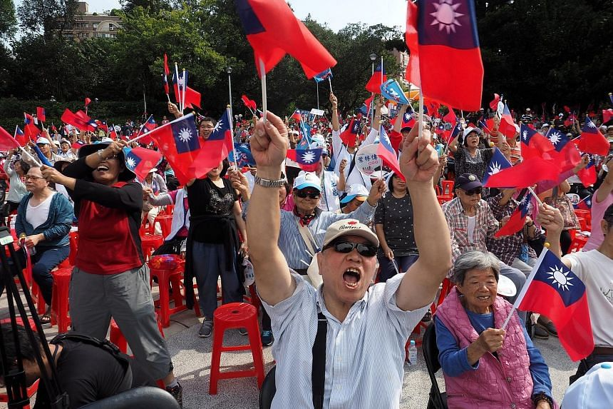 Opposition Kuomintang supporters waving party flags at a campaign rally in Taipei on Sunday.