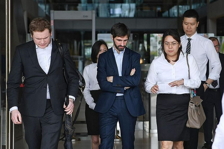 """B2C2 co-founder Maxime Boonen (centre), with his lawyers at the court yesterday. The electronic market maker is suing cryptocurrency exchange operator Quoine over a """"unilateral reversal"""" of orders on its platform."""