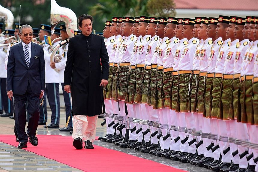 Malaysian Prime Minister Mahathir Mohamad (left) and Pakistani Prime Minister Imran Khan inspecting a guard of honour at the Prime Minister's Office in Putrajaya, Malaysia, yesterday. Mr Khan, whose two-day visit ended yesterday, was on his first vis
