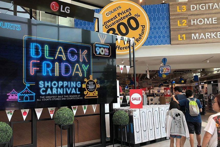 For last year's Black Friday sale, a long queue had formed outside Robinsons The Heeren in Orchard Road the night before the sale started (left). Courts is offering discounts of up to 23 per cent this year (below left).