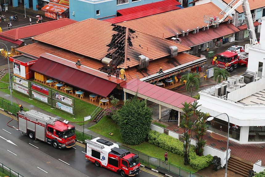 Above: Flames seen inside one of the stalls at the coffee shop in Jurong West Street 91 yesterday morning. Right and far right: Some roof tiles were dislodged in the blaze and fell onto the stalls below. Firefighters put out the fire at about 9.20am.
