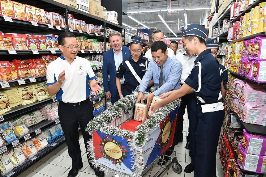 Minister for Social and Family Development Desmond Lee launching the Boys' Brigade Share-a-Gift 2018 project by donating some items yesterday at FairPrice Xtra Jurong Point. Also at the launch were Mr Seah Kian Peng (left), chief executive of NTUC Fa