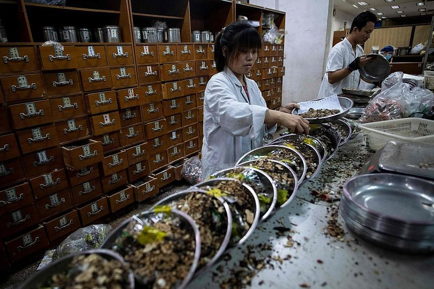 A woman mixes medicine in the Yueyang Hospital pharmacy, part of the Shanghai University of Traditional Chinese Medicine. With a history going back 2,400 years, traditional medicine remains popular in China despite access to Western pharmaceuticals.