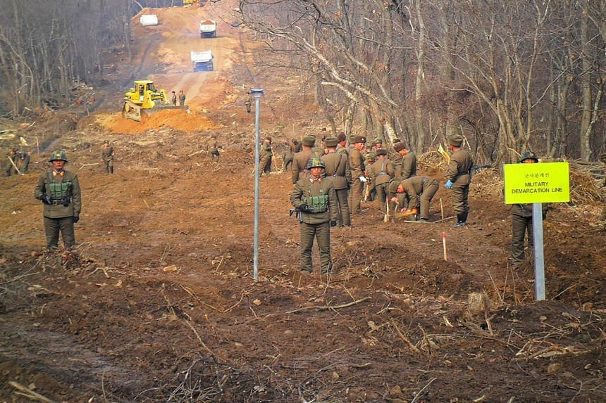 North Korean soldiers working near the Military Demarcation Line to construct a tactical road to support a joint war remains recovery project in the Demilitarized Zone dividing the two Koreas in Cheorwon.