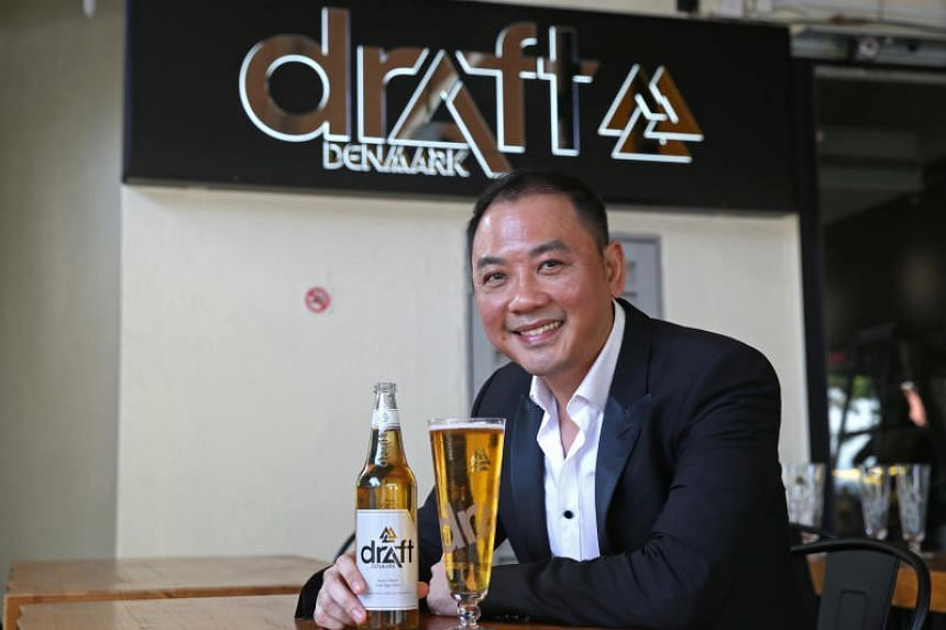 Sam Lim, chief executive of No Signboard Seafood, with a Draft Denmark beer, the signature brand of Danish Breweries which the company bought.