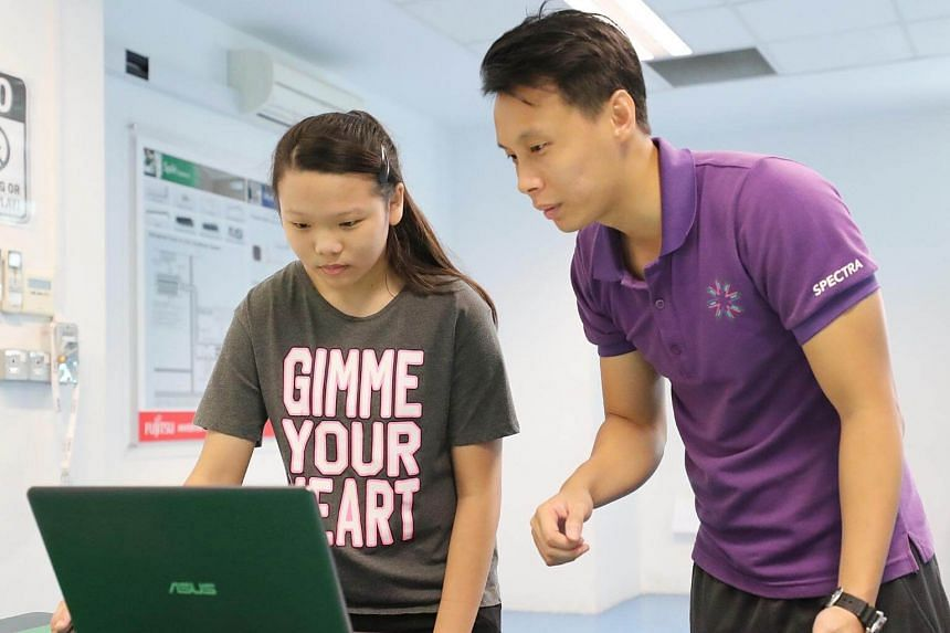 Mr Aaron Poh, 32, a vocational education teacher in Spectra Secondary School, shows Sharon Tan the websites and games she will learn to design if she enrolls in the school.