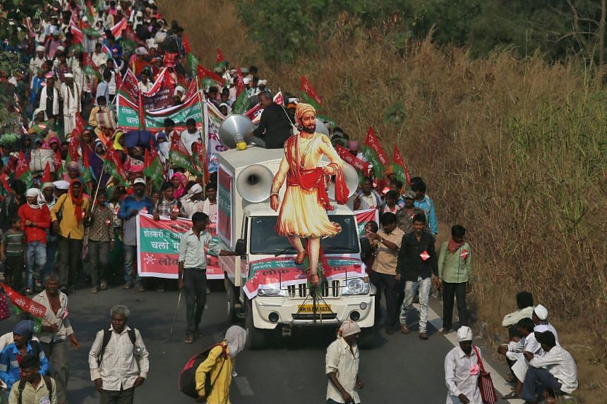Farmers march along with a vehicle during a protest rally demanding better price for their produce and total waiver of agricultural loans, in Mumbai on Nov 21, 2018.
