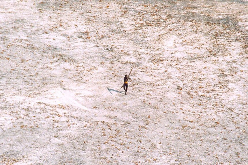 A Sentinel tribal man aiming his bow and arrow at an Indian Coast Guard helicopter in 2004. Indian authorities said it may take some time to retrieve the body of an American who was killed on North Sentinel Island.